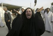 An Iraqi woman attends the funeral of a relative Friday at a cemetery in Najaf, Iraq. U.S. forces backed by attack aircraft killed at least 25 people north of Baghdad on Friday in an operation targeting a cell accused of smuggling weapons from Iran, the military said.