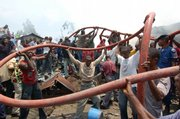 Local volunteers pass a fire hose to help firefighters douse debris at the site of a cargo plane crash Thursday in Kinshasa, Congo. A cargo plane smashed into a residential neighborhood in Congo's capital just after takeoff from the international airport Thursday, killing at least 25 people and engulfing homes in flames.