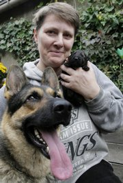 Gerlinde Schultze, 46, from Berlin, poses with her 1-week-old purebred East German shepherd puppy, Xaver, and Xaver's mom, Virginia. As the country celebrates 17 years of reunification, some animosities between the East and West remain, including the fight over which German shepherds are best.