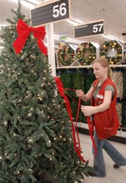 Whitney Baker, Lawrence, a floor sales associate at Westlake Ace Hardware, 711 W. 23rd St., decorates a Christmas tree display in the store Tuesday evening. It's only a few days since Columbus Day, and retailers across the country are already offering Christmas items for sale.