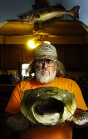 "Hoyt resident Michael Corrigan is no stranger to the world of handfishing, otherwise known as ""noodling."" Here he shows off the head of a 70-pound flathead he caught three years ago on the Red River in Oklahoma."