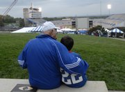 Former KU football coach Don Fambrough, left, hugs 10-year-old Jack Powell as they sit on a bench overlooking Memorial Stadium in this 2007 file photo. Former KU football players who played under Fambrough presented him with the bench in his honor during a dedication ceremony.