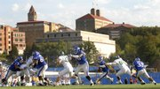 Underneath the backdrop of the Kansas University skyline, the Jayhawk offensive line provides just enough cover for quarterback Todd Reesing (5) to scramble against Baylor.