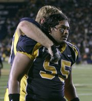 California's Zack Follett puts his arm around teammate Noris Malele (55) after the Golden Bears lost to Oregon State.