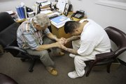 Volunteer mentor Lloyd Knapp, left, prays with inmate Tony Gonzales as part at the Carol Vance Unit, a faith-based prison facility in Richmond, Texas.