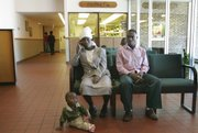 Sadiki Sirivesi sits with his wife, Habonimana, and their year-old son, Baraka, in the Samuel U. Rodgers Community Health Center lobby in Kansas City, Mo. The family of African refugees, shown in August, was waiting for Baraka to receive a physical.