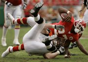 Cincinnati defensive end Justin Smith pulls down Kansas City Chiefs running back Larry Johnson (27).