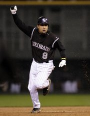 Colorado Rockies catcher Yorvit Torrealba celebrates as he rounds the bases after hitting a three-run home run in the sixth inning off Arizona Diamondbacks pitcher Livan Hernandez in Game 3 of the National League championship series. Colorado won, 4-1, Sunday in Denver to take a 3-0 lead in the best-of-seven series.