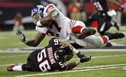 New York Giants running back Brandon Jacobs (27) is brought down by Atlanta Falcons linebacker Keith Brooking in the second quarter. The Giants routed the Falcons, 31-10, Monday in Atlanta.