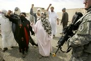 Civilian role players chant at Army soldiers during a training exercise in a mock Afghan village at Fort Riley. Civilian actors play the part of native villagers in the exercise to help train U.S. soldiers to deal with Afghan people.