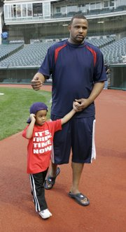 Cleveland pitcher C.C. Sabathia, right, walks with his son, C.C. Sabathia III, following an interview before baseball practice Wednesday in Cleveland. The Indians will meet Boston in Game 5 of the ALCS tonight in Cleveland.