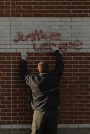 A custodial worker scrubs paint off the north side of Free State High School on Thursday morning.
