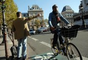 A man hitchhikes while another rides his bicycle Thursday in Paris. A public transport strike billed as France's biggest in years was in full swing, with commuters forced to walk, pedal or drive to work in large numbers, and many are thought to have stayed home.