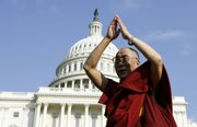 The Dalai Lama gestures on the West Steps of the Capitol on Wednesday in Washington following a ceremony where he received the Congressional Gold Medal. President Bush personally presented the medal and used the opportunity to advocate for religious freedom.