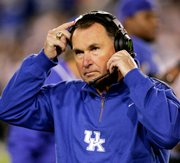 Kentucky football coach Rich Brooks adjusts his headset during a September game in Louisville, Ky.