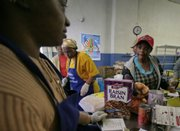 Marcia Watkis, far left, a volunteer at the Bedstuy Campaign Against Hunger, a food pantry that lets people in need shop for their own items, checks groceries for Merna Smith, right, Wednesday in the Brooklyn borough of New York.