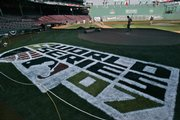 The grounds crew works behind the freshly painted World Series logo at Fenway Park. The Red Sox will entertain Colorado in Game 1 of the baseball World Series Wednesday.