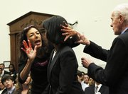 Secretary of State Condoleezza Rice, center, is confronted by CodePink member Desiree Anita Ali-Fairooz, her hands painted red, as Rep. Tom Lantos, D-Calif., right, Chairman of the House Foreign Relations Committee, right, intervenes. The protest occurred before Rice testified regarding U.S. policy in the Middle East, where she spoke about Iraq, Iran and the Israel-Palestinian conflict Wednesday on Capitol Hill in Washington. Ali-Fairooz was charged with assault on a federal officer and three other counts. After she was taken outside the hearing room, Ali-Fairooz smeared her painted hands on the hallway wall. A crew of Capitol painters was dispatched to paint over the marks.