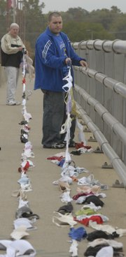 Hundreds of bras were strung across the Kansas River Bridge to raise breast cancer awareness. Hank Booth and Ian Rombough helped put up the display Friday.