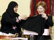 "U.S. first lady Laura Bush admires a head scarf presented to her Wednesday by Saudi Dr. Samia al-Amoudi, left, during participation in a ""Breaking the Silence"" coffee with a cancer survivors group in Jiddah, Saudi Arabia. Bush&squot;s trip to Saudi Arabia, her first to the oil-rich kingdom, is part of a regional tour that aims to highlight the need for countries to share their resources and unite in the fight against breast cancer."