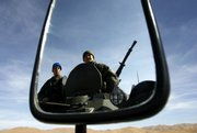 Turkish soldiers are reflected in a mirror Thursday as they ride on an armored vehicle during a daily patrol in Yuksekova, in the Hakkari province, near the Turkish-Iraqi-Iranian border in southeastern Turkey. A high-level Iraqi delegation was expected to visit Ankara on Thursday after Turkey's top leadership recommended the government take economic measures to force Iraqi cooperation against Kurdish rebels and Turkey considered a possible military cross-border offensive.