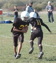 Sixth-grade Cougar Anthony Riley takes a hand-off from quarterback Adrian Hill.