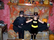 Collin Harris, age 8 and Rylee Harris, age 6 dressed up for Halloween as Batman and Batgirl in front of our spooky batcave fireplace 2007.