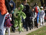Pinckney School kindergartner Eli Cohavi, in a green dragon suit, skips down the sidewalk with his class Wednesday on the way to Lawrence Memorial Hospital for Halloween fun.