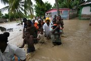 Residents struggle to cross a flooded street because of heavy rains caused by Tropical Storm Noel on Tuesday in Port-au-Prince, Haiti. Floods and mudslides across the region have killed at least 22 people.