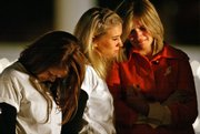 Meredith Yelton, right, identical twin of beach house fire victim Emily Yelton, is comforted by her sister's Delta Zeta sorority sisters during a vigil Wednesday at Clemson University in Clemson, S.C. Seven people were killed in the fire.