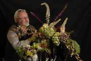 Several natural elements like winterberry and holly can be used to create indoor floral and plant arrangements to last through the holiday season. Pictured with the arrangement is John McCaffrey, owner of BitterSweet Floral and Design, 1407 Mass.