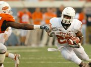 Texas running back jamaal Charles, right, finds a gap in the Oklahoma State defensive line. Charles scored three touchdowns, including two in the fourth quarter, in the Longhorns' 38-35 comeback victory against the Cowboys on Saturday in Stillwater, Okla.