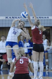 KU's Savannah NoyeS (18) spikes the ball for a kill on game point during the first game of KU's Big 12 home match against Oklahoma on Saturday.