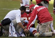 Trainers look after Kansas CIty Chiefs running back Larry Johnson after he was hurt in the fourth quarter of the Chiefs' 33-22 loss to Green Bay. The Chiefs said after Sunday's game in Kansas City, Mo., that Johnson might not return next week.