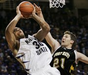 Kansas State forward Michael Beasley, left, shoots over Fort Hays State forward Ryan Herrman (21). Beasley, a freshman, scored 35 points Saturday against the Tigers, Kansas University's opponent tonight.
