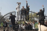 Pakistani lawyers climb on the closed gates of the District Courts chanting anti-Musharraf slogans in Multan, Pakistan. Lawyers again clashed with police as President Pervez Musharraf's government considered when to hold elections amid growing international pressure to end emergency rule and restore democracy.