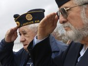 American Legion members Corky Reed, left, and Arthur Barton salute the flag during a Veterans Day ceremony.