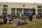 Kansas University student football fans wait Monday in front of Allen Fieldhouse for tickets to the KU-Missouri game Nov. 24. Ryan Leiker passed the time by tossing a football to friends as he rested in the grass. Hundreds of KU students camped out all night to pick up tickets they had purchased for the game.