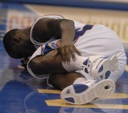 Kansas guard Sherron Collins grabs his ankle after hitting the deck. Collins returned to the game after the injury Sunday, but had surgery Monday to repair a pre-existing stress fracture.