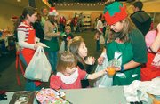 Stephanie Brown, right, helps Maria Copp, center, and Maleah Zumaly select gifts during the 2006 Children's Holiday Shop at the Lawrence Arts Center, 940 N.H. This year's event is Dec. 7-8.