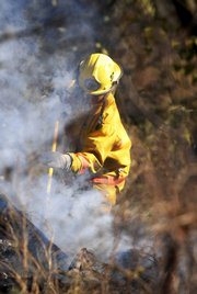 A firefighter with the Wellsville Fire Department works to extinguish a grass and barn fire on Friday south of Eudora. Firefighters brought the rural fire under control by early afternoon. No one was injured in the blaze. Much of northeast Kansas is in a burn ban because of the recent dry spell.