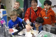 Gabi Reyes gets a laugh as Brandon Timmons, 8, left, and Edward Reyes, 8, play with goop while Brody Riemann, 10, far left, and Andrew Reyes, 3, watch at Kansas University's Carnival of Chemistry at Mallot Hall. The carnival was one of two science-themed events Sunday at KU.