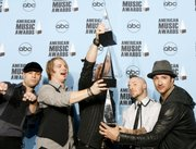 The musical group Daughtry shows off the awards for  favorite pop/rock album, adult contemporary artist and breakthrough new artist  at the American Music Awards in Los Angeles. Band frontman Chris Daughtry is at center.