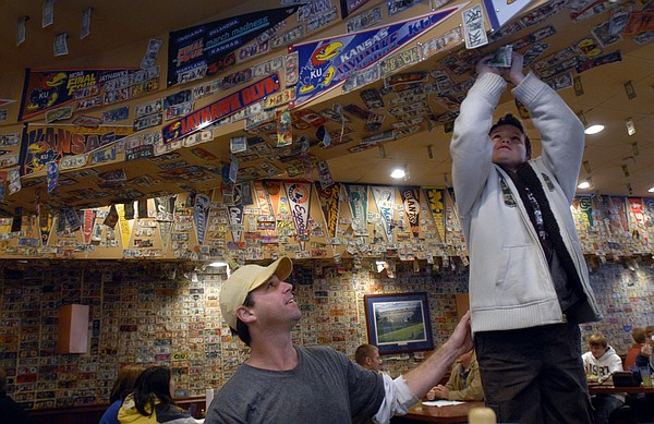 Kyler Carpenter, Topeka, steadies his son, Trevor, 8, as he secures a decorated dollar bill to the ceiling of Jefferson's Restaurant, 743 Mass., during the lunch rush Wednesday. Jayhawk fans planning to watch Saturday's Kansas-Missouri football game will stake their claims to seats at their favorite local bars and restaurants.