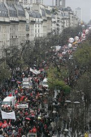 Thousands of civil servants demonstrate along a boulevard in Paris. Civil servants, from teachers to postal workers, began a mass walkout across France on Tuesday, the seventh day of a transport strike that has caused havoc on French rails.