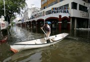 A man uses a boat to cross a flooded avenue in Villahermosa, Mexico, in this Nov. 8 file photo. A planned levee project funded largely by the federal government was not built by the state of Tabasco, and questions have arisen as to where the money went.