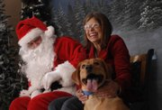 Janet D'Ercole, of Lawrence, right, laughs about her nervous Golden Retriever mix, Andy, while having their picture taken with Santa Claus at the Lawrence Humane Society, 1805 E. 19th St. They were attending the fundraiser Santa Paws, which benefits the shelter.