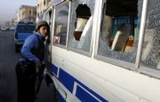 An Iraqi police officer inspects a minibus damaged in a bomb explosion Thursday in Baghdad. A bomb left in a minibus went off early Thursday morning, killing one person, and injuring another five, police said.