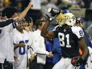 Dallas receiver Terrell Owens throws popcorn in his face after scoring a second-quarter touchdown. The Cowboys defeated Green Bay, 37-27, on Thursday night in Irving, Texas.
