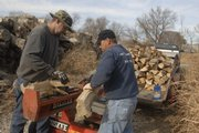 Don Cottrell, left, and Darryl James split firewood in North Lawrence. Cottrell said he has about 225 customers in the area who regularly buy wood by the cord - a pile that measures 8 feet long, 4 feet wide and 4 feet high.